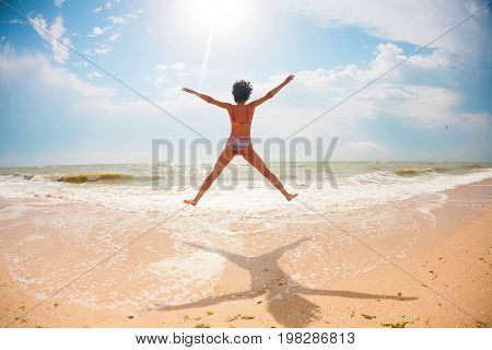 A Girl Is Jumping On The Ocean Shore.