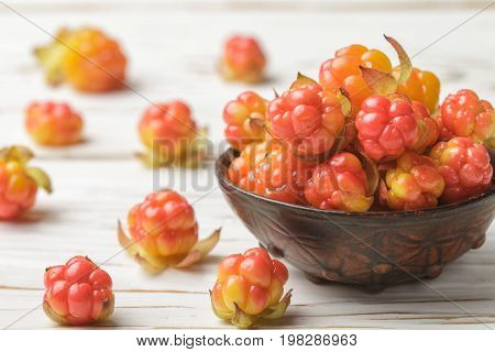 Fresh Organic Berry Cloudberries In A Clay Bowl On Light Wooden Background. Selective Focus