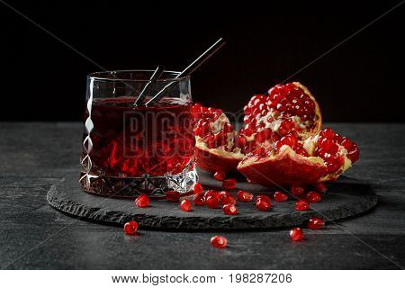 A beautiful composition of a glass of alcoholic garnet drink and a cut pomegranate on a round plate on a saturated black background. Exotic summer fruity red drink with straws and delicious garnet.