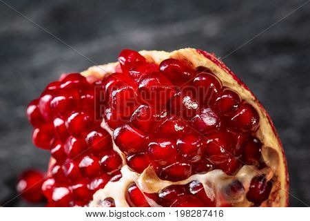 A close-up of a beautiful, ripe, juicy, colorful garnet on a black background. A piece of a tasteful tropical pomegranate full of sour red seeds. Health, organic, nature and antioxidant concept.