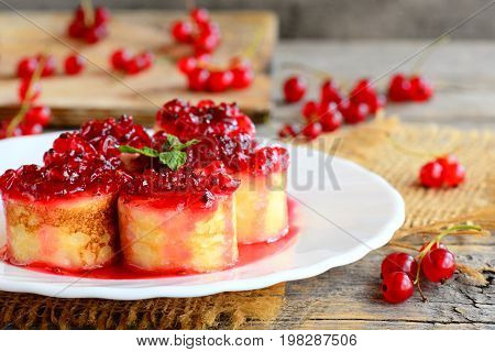 Sweet crepes sushi rolls with redcurrant confiture on a white plate and a vintage wooden table. Stuffed crepes dessert recipe. Easy Easter breakfast idea