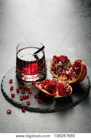 Delicious, organic and healthful pomegranate juice in a fancy glass and a garnet grain on a black tray on a light gray background. Healthful bittersweet beverage and nutritious garnet seeds.