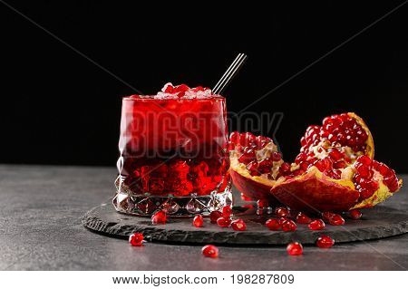 A red berry cocktail with crushed ice and a part of a pomegranate on a black background. Non-alcohol antioxidant beverage. A grain of bittersweet garnet.  Expensive delicacy drinks for gourmets.