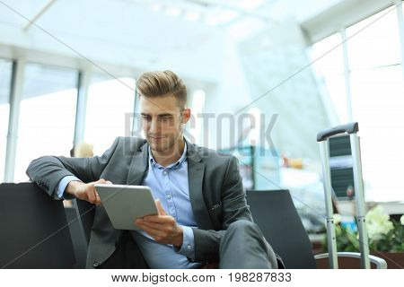 Businessman using digital tablet in airport departure lounge