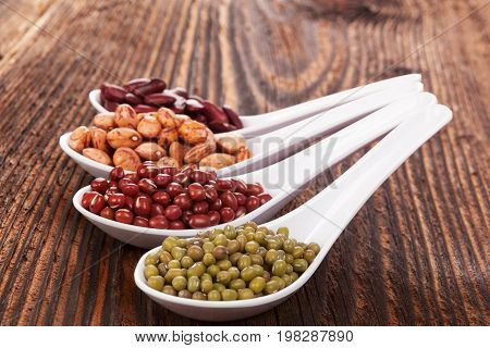 Various healthy legumes in spoons on wooden table. Mungo beans. Healthy eating.