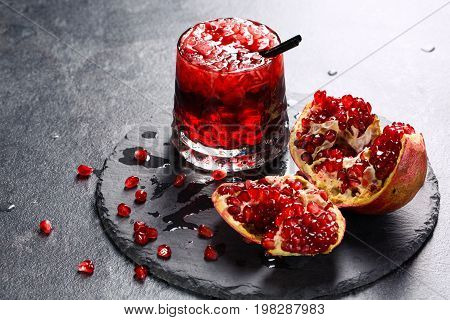 A composition of a non-alcohol beverage with garnet juice, ice and a straw. A cracked pomegranate and a glass of red juice on a tray on a gray background. Delicious garnet products full of vitamins.