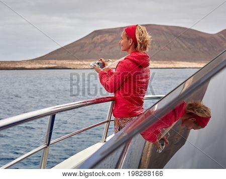 happy young woman enjoying boat trip to La Graciosa island near Lanzarote, Canary islands, Spain