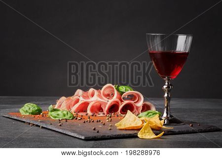 Sliced prosciutto, spicy chips and a glass of red wine on a black table backgrund. Appetixing traditional italian wine with restaurant snacks. Delicatessen, luxury, celebration concept. Copy space.