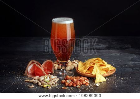 A glass of dark beer with nutritious peanuts and pistachios, tasteful jamon and nachos ships in a plate. Appetizing and cold beer with foam. Brewery, cuisine, restaurant business concept. Copy space.