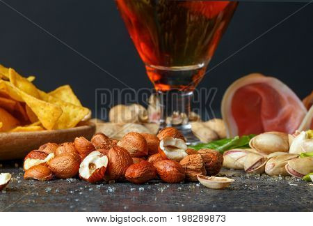 A set of tasteful and nutritious traditional snacks next to a big pint of dark beer on a black table background. Nachos chips in a plate and peanuts. Sliced ham and appetizing pistachios. Copy space.