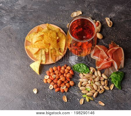 A view from above on different tasteful snacks and a tall glass of dark beer on a black table background. A plate of chips, crunchy nuts, spinach leaves and cut prosciutto. Delicious refreshing beer.