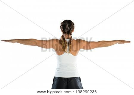 Rear view of female athlete with arms outstretched exercising against white background