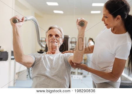 Strong arms. Smiling pensioner feeling happiness while training and listening recommendations