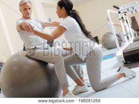 Train coordination. Strong sporty woman standing on left knee and supporting arms while looking at her patient
