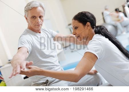 Do it together. Serious pensioner pressing lips and looking at his hand while sitting on bib fitness ball