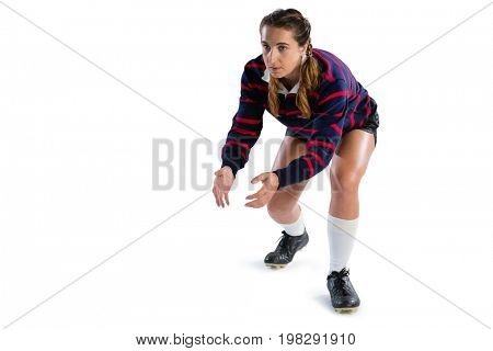 Full length of female rugby player in catching position against white background