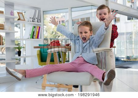 Boy as business executives pushing his colleague on chair in office