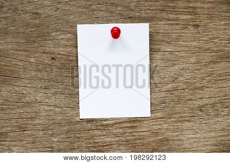 White paper pin on brown wood background for memo notice or to do list