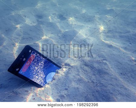 Mobile phones on the sand under the sea water near the beach.