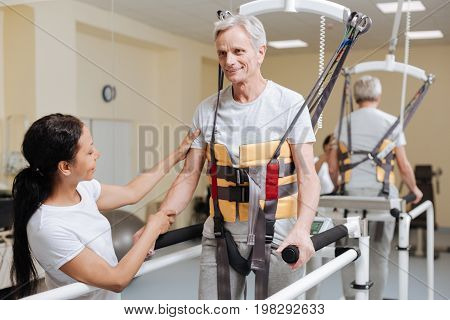 Special equipment. Confident retirement being well-equipped while doing exercises and keeping smile on his face