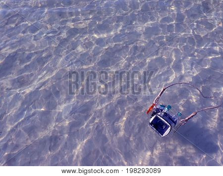 Compact camera and housing floating on the sea with reflections surface.