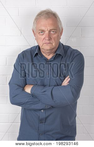 Vertical image of an annoyed mature man standing against a white brick background