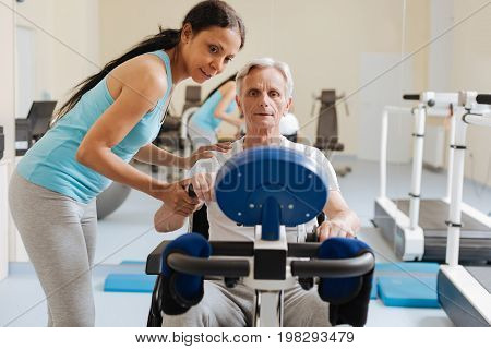 Concentrate on it. Enigmatical young trainer keeping smile on her face and keeping her back bent while talking to her patient