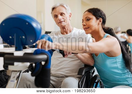 Healthy habits. Positive brunette keeping smile on her face and pointing at timer while talking to her patient
