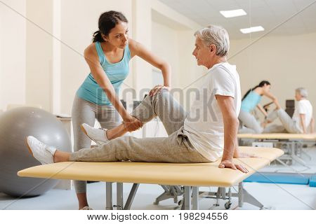 Stretching tasks. Competent trainer standing in front of her patient and looking forward while trying to bent right leg of her visitor