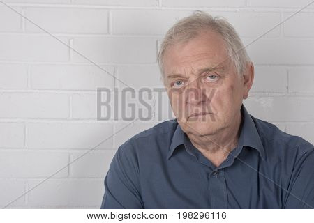 Annoyed mature man with a white brick background and copy space