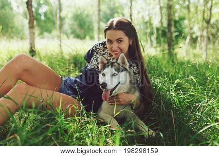 Beautiful woman with husky outdoors.Happy brunette woman with smiling siberian husky dog sitting in a poppy field on a sunny day on a walk with dog