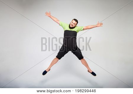 studio portrait of a happy mature man jumping over white background. Man dressed in a green T-shirt and black funny pants