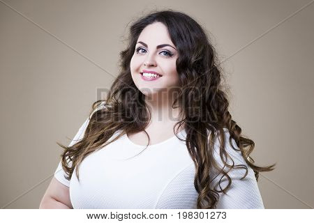 Happy plus size fashion model in casual clothes fat woman on beige studio background overweight female body