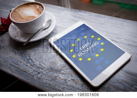 Free roaming text on European Union flag against cappuccino and digital tablet on table