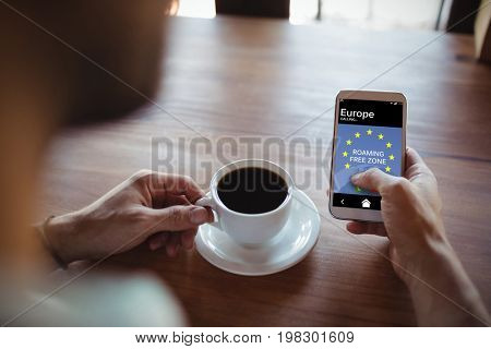 Roaming free zone text and European Union flag on mobile screen against man using mobile phone while having coffee