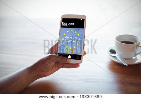 Good bye roaming text and European Union flag on mobile screen against cropped hand of woman using phone at table