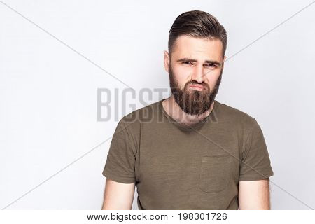 Portrait of unhappy sad bearded man with dark green t shirt against light gray background. studio shot.