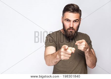 Hey You! Portrait of serious bearded man with dark green t shirt against light gray background. studio shot.