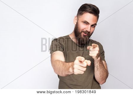 Hey you! Portrait of happy bearded man with dark green t shirt against light gray background. studio shot.