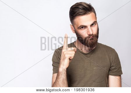 Portrait of serious bearded man with warning finger and dark green t shirt against light gray background. studio shot.