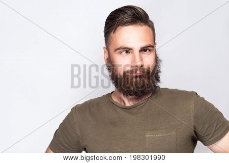 Portrait of crazy cross eyed bearded man with dark green t shirt against light gray background. studio shot.
