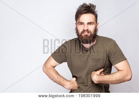 Portrait of funny crazy bearded man with dark green t shirt against light gray background. studio shot.