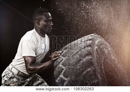 Black background against military soldiers exercising with tyre