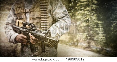 Road through forest against military soldier carrying a rifle
