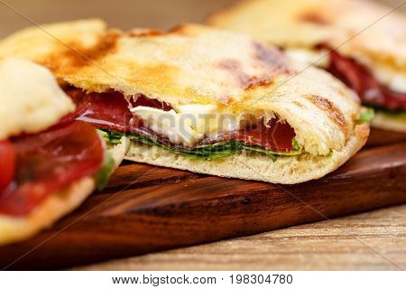 Sliced pizza calzone whith ham on wooden board on wooden table.