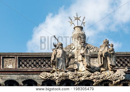 Shanghai, China - Nov 6, 2016: In the 600-year-old Old City God Temple. Statues of the Three Immortals on standing cloud as decorations on roof. These are patron saints of Chinese mythology.