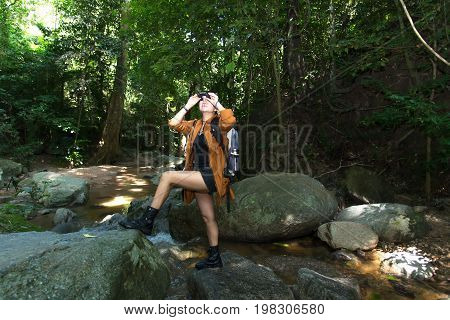 Women hiker with backpack checks map to find directions and look binoculars in wilderness area at waterfalls and forest. Travel Concept