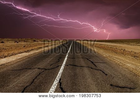 Stormy country road at night, with lightning strikes.