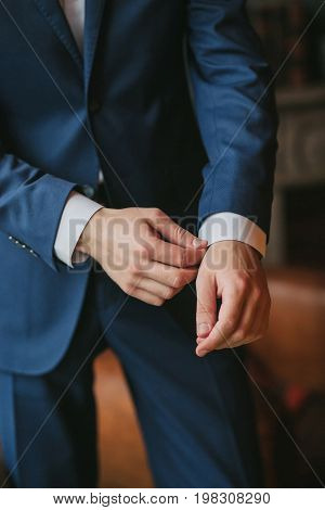 A young man in a blue suit adjusts his shirt cufflinks. Hands close-up on a brown chair background