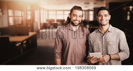 2 smiling men posing with a digital tablet  against table and empty chairs in office